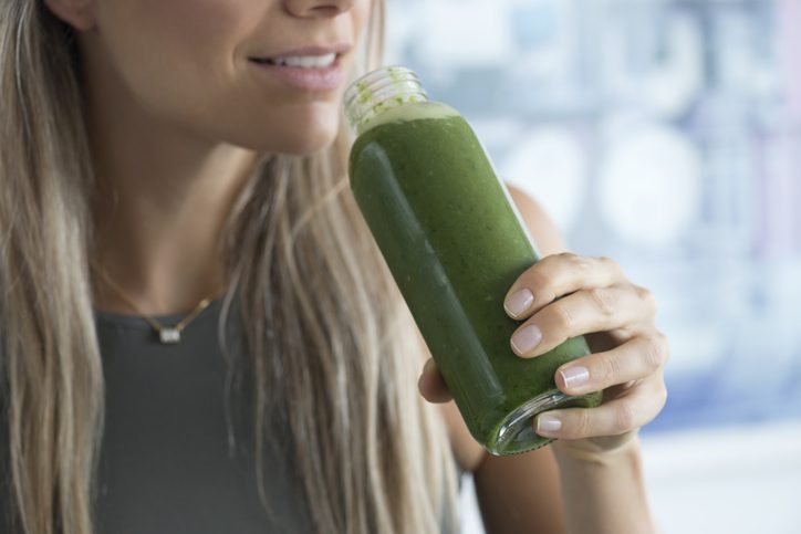 woman holding a healthy drink made from green fruits and vegetables