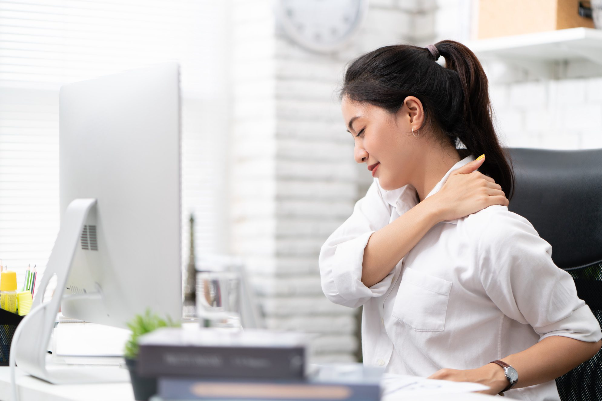 a professional woman sitting while holding her shoulder