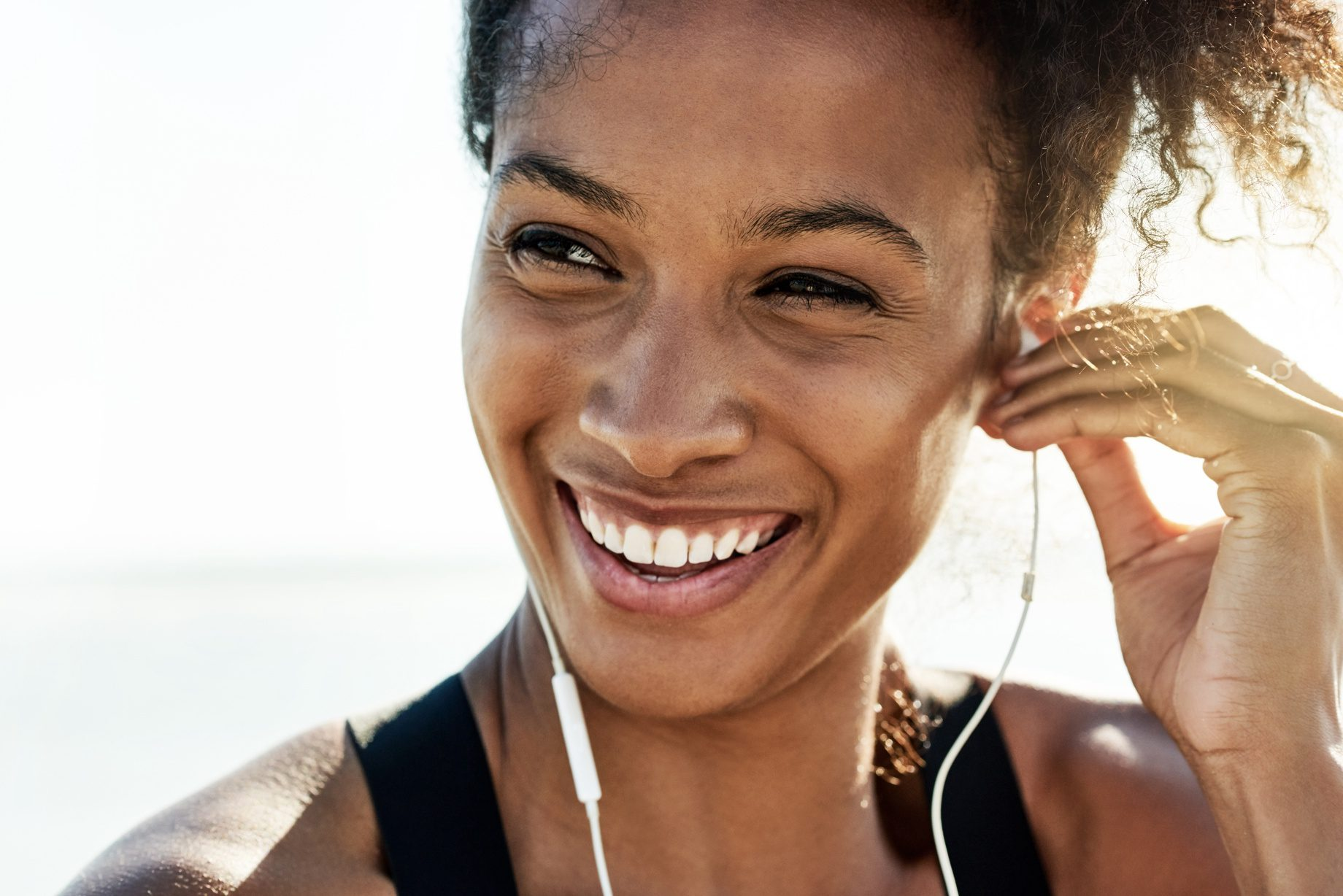 a woman smiling while listening to music